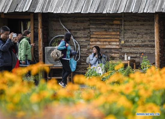 Tourists visit a homestay at kanas scenic spot in Altay, northwest China's Xinjiang Uygur Autonomous Region, Sept. 26, 2019. More and more tourists choose to experience homestay with strong local characteristic in Xinjiang. (Xinhua/Wang Fei)