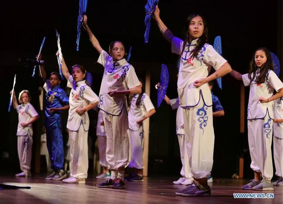 "Students of Intercultural Montessori Language School perform dance ""Kung Fu Fan"" at the 2019 U.S.-China Students Gala in Chicago, the United States, on Oct. 19, 2019. The 2019 U.S.-China Students Gala, featuring student performance groups from universities across the Midwest, was staged at the Logan Center in the University of Chicago on late Saturday with an aim at promoting cultural exchanges between the two countries. (Xinhua/Wang Ping)"