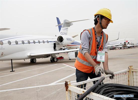 An exhibitor works near aircrafts to be displayed in the Asian Business Aviation Conference and Exhibition (ABACE) at Shanghai Hongqiao International Airport in east China's Shanghai, April 16, 2018. The ABACE is expected to be held here from April 17 to 19, attracting over 170 companies around the world to participate in the exhibition. (Xinhua/Chen Fei)