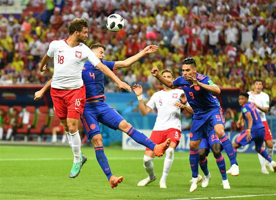 Bartosz Bereszynski (1st L) of Poland competes for a header with Santiago Arias (2nd L) of Colombia during the 2018 FIFA World Cup Group H match between Poland and Colombia in Kazan, Russia, June 24, 2018. (Xinhua/Lui Siu Wai)