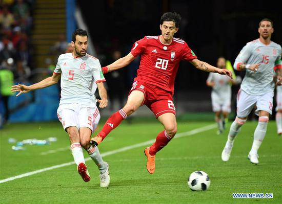 Sergio Busquets (L) of Spain vies with Sardar Azmoun (C) of Iran during a Group B match between Spain and Iran at the 2018 FIFA World Cup in Kazan, Russia, June 20, 2018. (Xinhua/Liu Dawei)