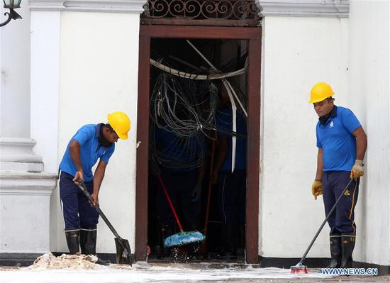 Workers clear away debris and shattered glass amid tight security outside St. Anthony's Church, one of the targets in a series of bomb blasts targeting churches and luxury hotels on Sunday in Colombo, Sri Lanka, on April 27, 2019. (Xinhua/A. Hapuarachchi)