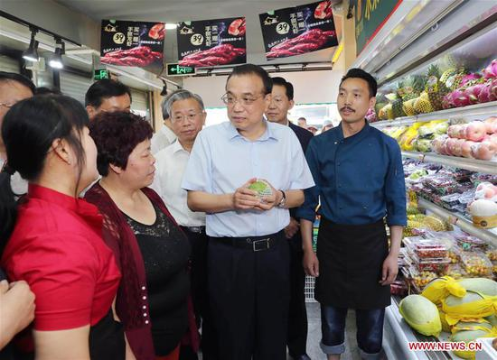 Chinese Premier Li Keqiang, also a member of the Standing Committee of the Political Bureau of the Communist Party of China Central Committee, learns about fruit prices when stopping by a fruit shop during an inspection in east China's Shandong Province, May 25, 2019. Li made an inspection tour to Weifang and Jinan in Shandong Province from Friday to Saturday. (Xinhua/Liu Weibing)