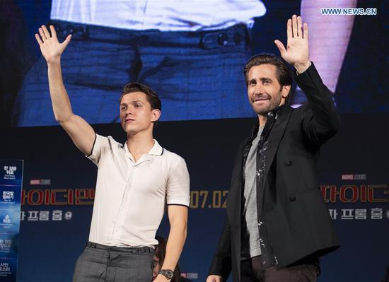 Actors Tom Holland (L) and Jake Gyllenhaal greet fans during a press conference of the film