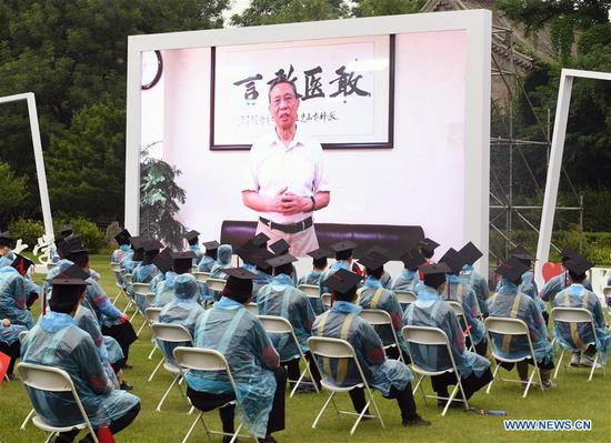 Graduates watch the video of a speech by Zhong Nanshan, a renowned Chinese respiratory specialist and alumni representative, at the commencement ceremony of Peking University in Beijing, capital of China, July 2, 2020. Peking University held its commencement ceremony in Beijing on Thursday. Due to COVID-19 prevention and control measures, a limited number of graduates attended the ceremony at nine venues on site while others participated online. (Xinhua/Ren Chao)