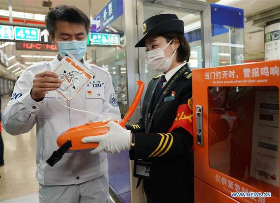A staff member of Beijing Emergency Medical Center demonstrates an automated external defibrillator (AED) to a subway worker in Beijing, capital of China, Oct. 27, 2020. Beijing started to equip its rail transit system with AED on Tuesday. By the end of 2022, all stations of the city's rail transit will be equipped with AED. (Xinhua/Zhang Chenlin)