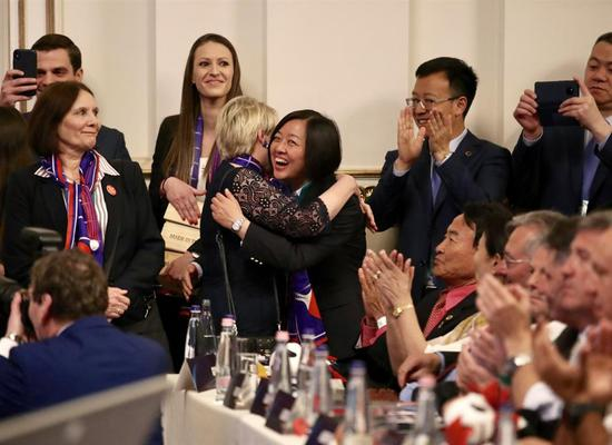 Liu Yi (center), vice president of Chinese Table Tennis Association, receives hugs as Chinese city of Chengdu won the bid to host the 2022 World Table Tennis Championships in Budapest on April 22, 2019.