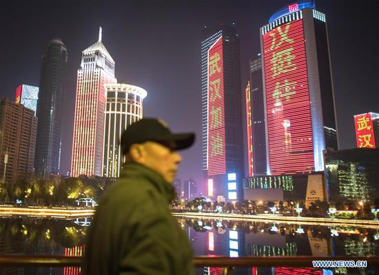 Photo taken on Jan. 31, 2020 shows buildings illuminated with slogans to cheer the city on in Wuhan, central China's Hubei Province. (Xinhua/Xiao Yijiu)