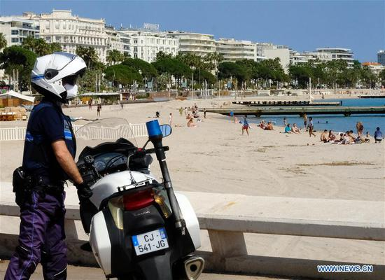 A policeman patrols at the seaside in southern France's Cannes, May 21, 2020. France on Thursday saw the death toll from the coronavirus increasing to 28,215 with 83 new deaths in the last 24 hours, lower than Wednesday's 110, according to figures released by the country's Health Ministry. As of Thursday, 318 new positive cases were detected, bringing the total of confirmed cases to 144,163. (Photo by Serge Haouzi/Xinhua)