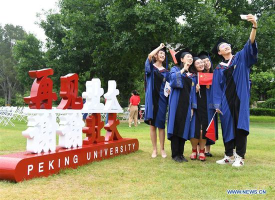 Graduates take a selfie after the commencement ceremony of Peking University in Beijing, capital of China, July 2, 2020. Peking University held its commencement ceremony in Beijing on Thursday. Due to COVID-19 prevention and control measures, a limited number of graduates attended the ceremony at nine venues on site while others participated online. (Xinhua/Ren Chao)