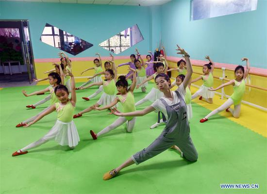 Children practice their body shapes at a dancing school in Lianyun District, Lianyungang, east China's Jiangsu Province, July 26, 2020. (Photo by Wang Chun/Xinhua)