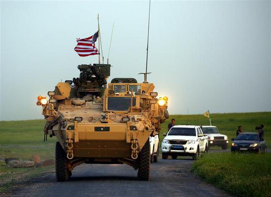 In this file photo taken on April 28, 2017, US forces, accompanied by Kurdish People's Protection Units fighters, drive their armored vehicles near the northern Syrian village of Darbasiyah, on the border with Turkey.
