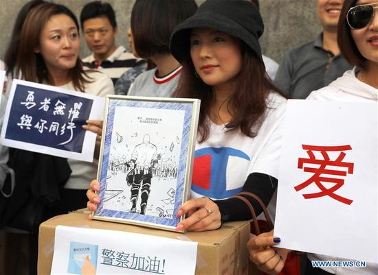 Residents gather outside Hong Kong Police Headquarters to offer goods and blessing cards, including a cartoon depicting a Hong Kong police officer, in Hong Kong, south China, Aug. 9, 2019. (Xinhua/Wu Xiaochu)