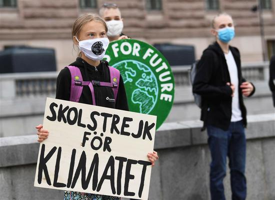 "Greta Thunberg holds a poster reading ""School strike for Climate"" on Friday in front of the Swedish Parliament."