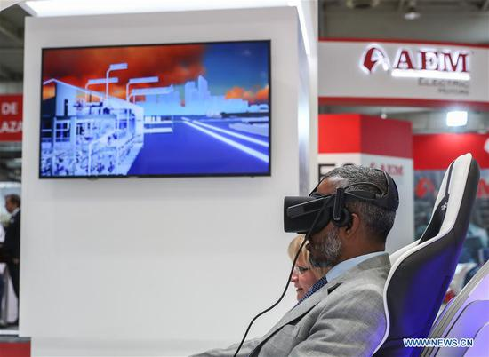 A visitor experiences VR device at the booth of China Aerospace Science and Industry Corporation at Hanover Fair 2018 in Hanover, Germany, April 24, 2018. Around 1,300 Chinese exhibitors participate in Hanover Fair this year. (Xinhua/Shan Yuqi)