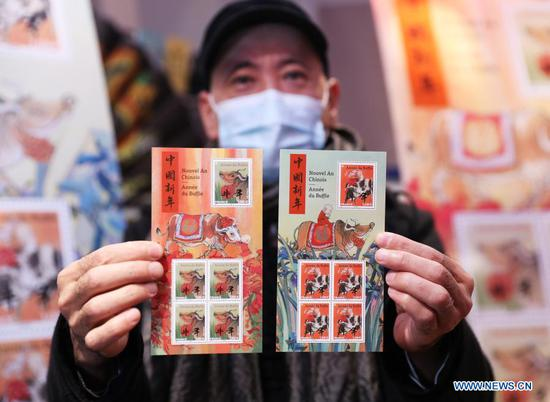 Paris-based Chinese artist Chen Jiang Hong displays the commemorative stamps themed on the Year of the Ox during the issuing ceremony in Paris, France, Feb. 6, 2021. The year 2021 is the Year of the Ox according to the Chinese zodiac. With Chinese culture and food becoming increasingly popular, people not only in China, but all over the world also take part in the Chinese New Year celebrations. (Xinhua/Gao Jing)