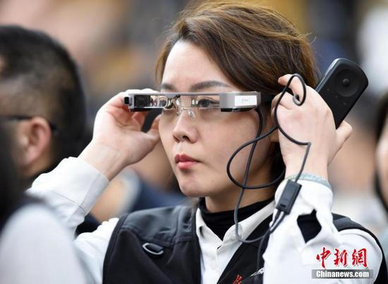 A reporter wears virtual reality (VR) glasses while covering the second session of the 13th National People's Congress at the Great Hall of the People in Beijing on Tuesday, March 5, 2019. The VR glasses can record the voice of the wearer, and the tiny camera installed on the frame of the glasses can capture high-definition videos. (Photo/China News Service)