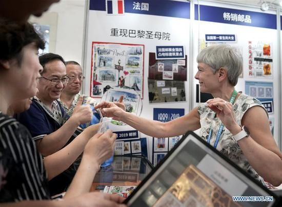Visitors talk with a representative of a French exhibitor during the 2019 World Stamp Exhibition held in Wuhan, capital of central China's Hubei Province, June 11, 2019. The 2019 World Stamp Exhibition kicked off here on Tuesday. Nearly 4,700 exhibits from more than 80 countries and regions are showcased during the event. (Xinhua/Cheng Min)