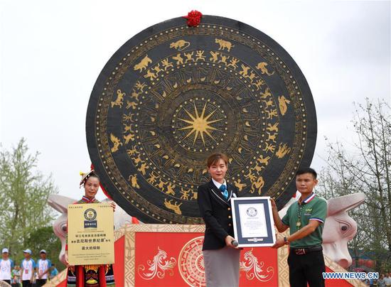 Staff demonstrate certificates beside a gigantic bronze drum in Huanjiang Maonan Autonomous County, south China's Guangxi Zhuang Autonomous Region, June 29, 2018. The drum measures 6.68 meters in diameter and weighs 50 tons. It was recognized as the largest bronze drum by Guinness World Records. (Xinhua/Zhou Hua)