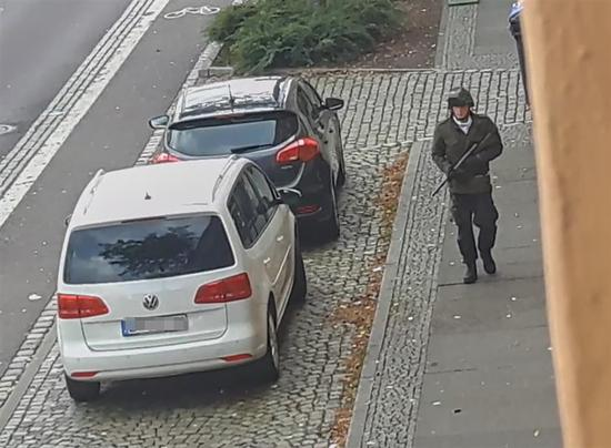 In this screenshot taken from a video by ATV-Studio Halle, a man walks with a gun in the streets of Halle an der Saale, eastern Germany, on October 9, 2019.