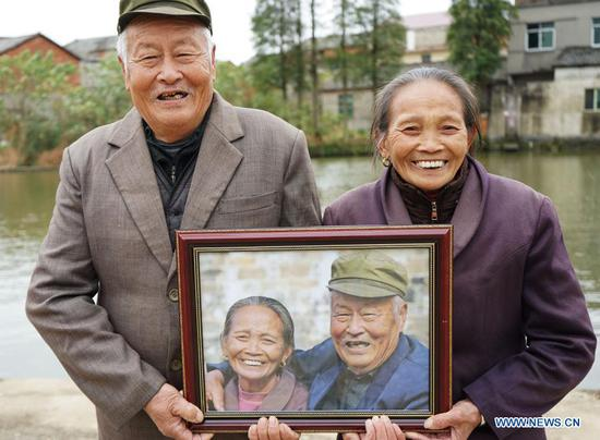 A local couple smile as they hold their photo in Xiawei Village of Youlan Town, Nanchang City, east China's Jiangxi Province, Nov. 22, 2020. Since 2014, volunteers from a non-profit organization in Nanchang City have kept on taking photos of smiling faces of farmers aged over 70 years old in nearby villages. The portait photos taken by volunteers were given to farmers for free. By far, the volunteers have taken nearly 4,350 people and 50,000 photos. They aim at collecting high-definition images of 10,000 farmers within 10 years. (Xinhua/Chen Chunyuan)