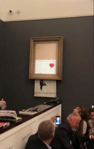 "Banksy's painting ""Girl with Red Balloon"" is seen shredded after its sale at Sotheby's auction in London, Britain on October 5, 2018 in this still image taken from a video obtained from social media on October 6, 2018. /Reuters Photo"