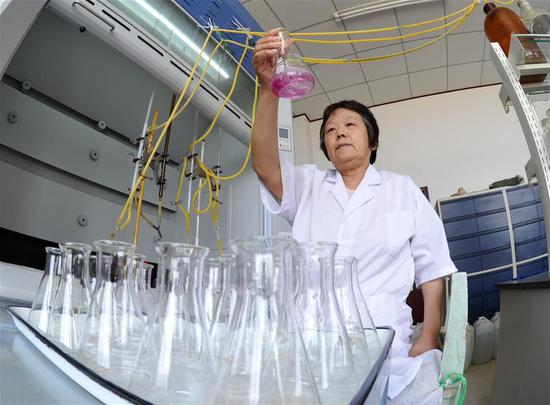 A staff member of Nanpi Eco-Agricultural Experimental Station of the Chinese Academy of Sciences (CAS) analyzes soil salinity in Nanpi County, north China's Hebei Province, June 12, 2018. Workers of the experimental station are busy sampling and calculating output of a project to boost agricultural innovation and increase crop production. (Xinhua/Mu Yu)