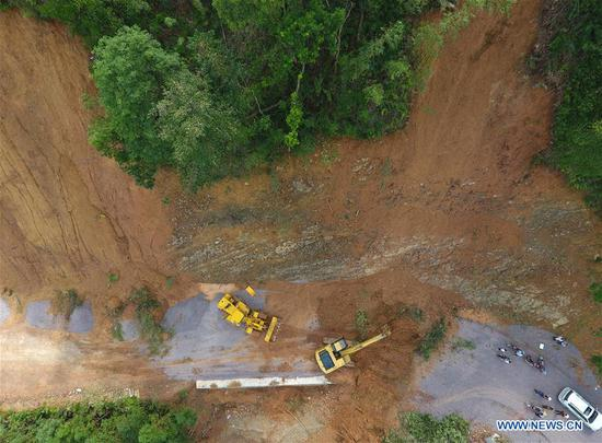 In this aerial photo taken on Sept. 19, 2018, workers clear a road damaged by Super Typhoon Mangkhut in Liuxiang Village of the Yao Autonomous County of Jinxiu in south China's Guangxi Zhuang Autonomous Region. (Xinhua/Lu Boan)