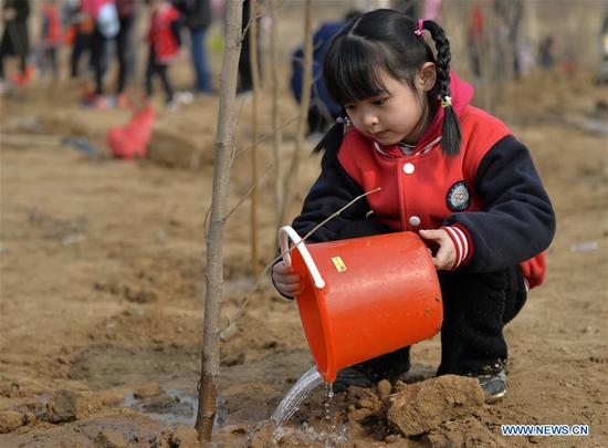A child waters a tree at Wuzhong Village in Qiaoxi District of Xingtai City, north China's Hebei Province, March 11, 2019. Students from Guoshoujing Primary School took part in a tree-planting activity to greet the upcoming Tree Planting Day, also known as Arbor Day, which falls on March 12 each year. (Xinhua/Mu Yu)