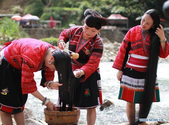 Women wash their long hair along the riverside in Huangluo Village of the Yao ethnic group in Longji Township of Longsheng County, south China's Guangxi Zhuang Autonomous Region, July 4, 2019. Women here have the tradition of keeping long hair. They use fermented rice water- the water after rinsing rice- together with natural ingredients such as tea seeds and orange peels to wash their hair. The natural shampoo keeps their hair healthy, smooth and shiny. (Photo by Huang Yongdan/Xinhua)