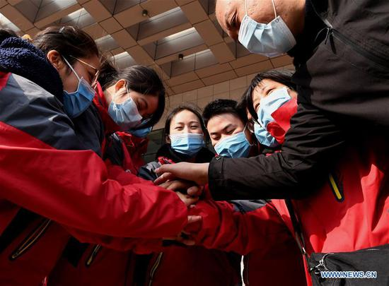 Medical workers cheer for each other before setting off for Wuhan in Hubei Province, in Zhengzhou, central China's Henan Province, Feb. 2, 2020. The second batch of 122 medical workers from Henan set off on Sunday to aid the coronavirus control efforts in Wuhan. (Xinhua/Li An)