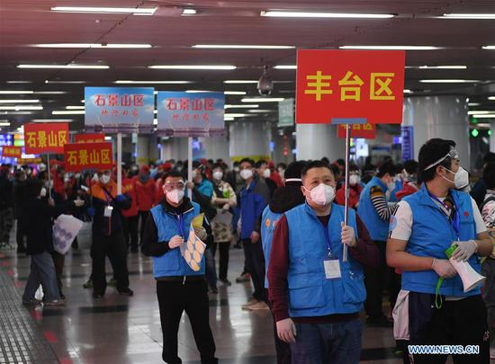 Staff members of all districts of Beijing pick up people returning from Hubei at the Beijing West Railway Station in Beijing, capital of China, March 25, 2020. The first batch of over 800 people stranded in virus-hit Hubei Province has arrived in Beijing Wednesday afternoon after Hubei lifted outbound travel restrictions in all areas except the capital city Wuhan starting from Wednesday. (Xinhua/Zhang Chenlin)