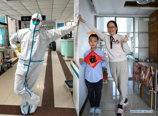Combo photo shows Si Daoyuan in the ICU of the Tonghua Central Hospital in Tonghua, northeast China's Jilin Province, Feb. 8, 2021 (L), and his wife Ni Lujia and their son Si Tongxun at their home in Changchun, northeast China's Jilin Province, Feb. 9, 2021 (R, photo taken by Yan Linyun). Si Daoyuan, 37, is an internist in the China-Japan Union Hospital of Jilin University. He arrived in Tonghua in January with a medical support team dispatched from his hospital to fight against COVID-19, and now works in the ICU of the Tonghua Central Hospital. He chose to work in the front line of the COVID-19 epidemic control during this Spring Festival with a strong faith that a reunion with family will not be far away. As a part of the preventative measures against COVID-19, China has encouraged people to stay locally for the Chinese New Year. Many Chinese chose not to go back to their hometowns for family gatherings, opting instead to stay where they were for the most important holiday of the year. Xinhua reporters helped those who didn't go back to their hometowns