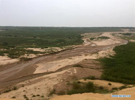 Photo taken on Aug. 1, 2018 shows a seasonal river channel at the Kubuqi Desert in Erdos, north China's Inner Mongolia Autonomous Region. Kubuqi, the seventh largest desert in China, is a good example of China's success in alleviating desertification. About 6,460 square kilometers of the Kubuqi desert has been reclaimed in the last 30 years. (Xinhua/Zhang Shanchen)