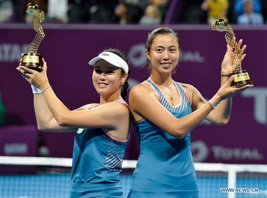 Hao-Ching Chan (R) and Latisha Chan of Chinese Taipei hold up the trophy during the awarding ceremony after the doubles final against Demi Schuurs of the Nederlands and Anna-Lena Groenefeld of Germany at the 2019 WTA Qatar Open in Doha, Qatar, Feb. 16, 2019. (Xinhua/Nikku)