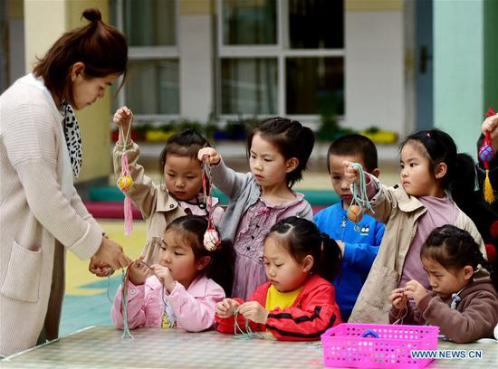 Children learn to knit a net for painted eggs under the guide of a teacher marking the upcoming