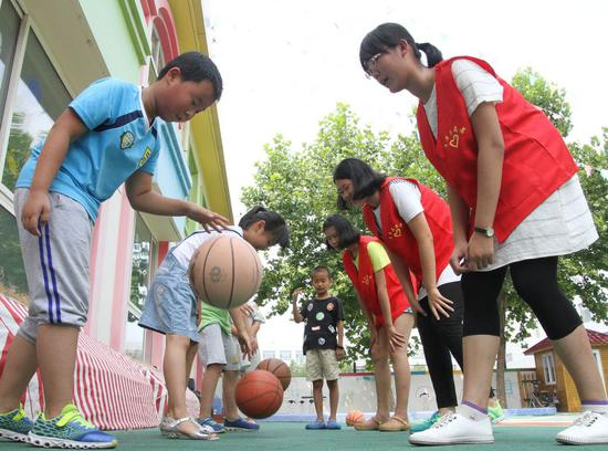 Kids compete in a basketball bouncing match at a community in Boxing County of Binzhou, east China's Shandong Province, Aug. 5, 2016. (Xinhua/Chen Bin)