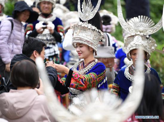 Tourists are greeted with wine when visiting Langde village of Miao ethnic group in Qiandongnan Miao and Dong Autonomous Prefecture of southwest China's Guizhou Province, Oct. 7, 2020. (Photo by Cai Xingwen/Xinhua)