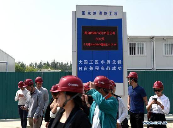 People walk past the countdown clock for the completion of the National Speed Skating Oval construction in Beijing, capital of China, May 9, 2018. The National Speed Skating Oval, which will host speedskating competitions during the 2022 Beijing Winter Olympic and Paralympic Games, is expected to be completed by the end of 2019. (Xinhua/Luo Xiaoguang)