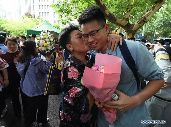 A parent kisses an examinee outside an exam venue at a middle school in Nanjing, capital of east China's Jiangsu Province, June 9, 2018. The national college entrance examination in Jiangsu ended on Saturday. (Xinhua/Sun Can)
