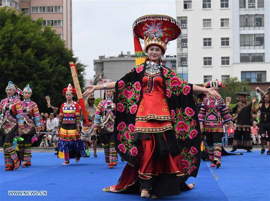 Women of Yi ethnic group present traditional costumes on a square during a folk costume show in Chuxiong, southwest China's Yunnan Province, Aug. 5, 2018. (Xinhua/Yang Zongyou)