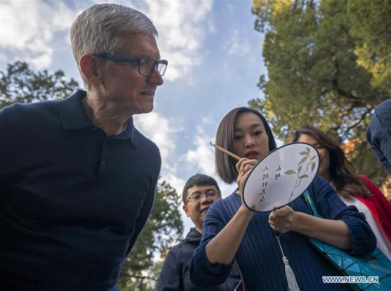 Apple's CEO Tim Cook looks at a woman writing calligraphy on a fan at Beijing Confucian Temple in Beijing, capital of China, on Oct. 10, 2018. Cook paid a visit to Beijing Confucian Temple and the Imperial College on Wednesday. (Xinhua/Cai Yang)