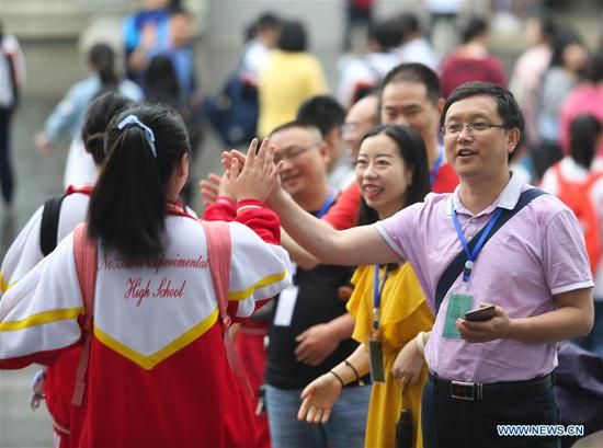 A teacher (R) cheers for examinees at an exam venue at the No. 10 Middle School in Guiyang, capital of southwest China's Guizhou Province, June 7, 2019. China's national college entrance examination, or Gaokao, started Friday this year. (Xinhua/Zhang Hui)