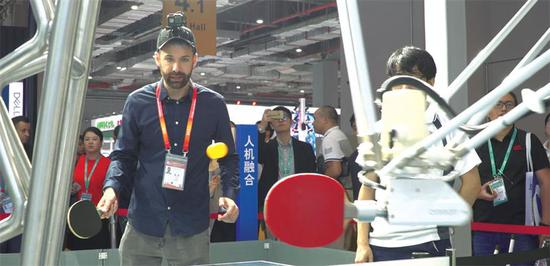 Andy Boreham plays against Omron's ping-pong robot.