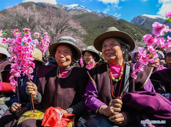 People watch folk art performance during a kick-off ceremony for tourism season in Gongbo'gyamda County, southwest China's Tibet Autonomous Region, April 15, 2018. (Xinhua/Liu Dongjun)