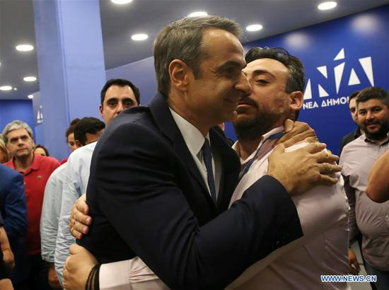 Greek main opposition New Democracy party leader Kyriakos Mitsotakis (Front) is greeted by a supporter in Athens, Greece, on May 26, 2019. Greek main opposition conservative New Democracy (ND) party leader Kyriakos Mitsotakis called Greek Prime Minister Alexis Tsipras to quit so that Greece will be led to early national elections, after the results of the European parliament and local parliament elections on Sunday. (Xinhua/Marios Lolos)