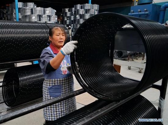 A staff member arranges bicycle rims at the Tangshan Jinhengtong Group in Lutai Economic Development Zone of Tangshan City, north China's Hebei Province, Oct. 14, 2020. In recent years, local authorities of Lutai Economic Development Zone in Tangshan have pushed forward the upgrading and industrial agglomeration of local bicycle components production companies. With more than 40 companies achieving a yearly revenue of about 5 billion yuan (about 745 million U.S. dollars), the bicycle component products have made their presence in both domestic and overseas market. (Xinhua/Mu Yu)