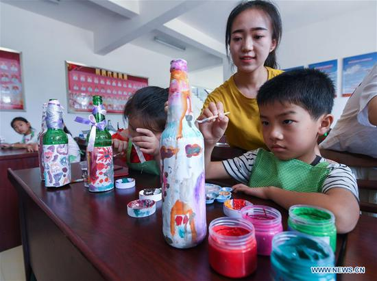 Students use waste materials to make ornaments under the guidance of volunteers during a class at a school in Lincheng Township in Changxing County, east China's Zhejiang Province, July 10, 2018. Volunteers from Hangzhou Normal University and government officials organized the class to teach students how to classify the garbage and reuse the waste. (Xinhua/Xu Yu)