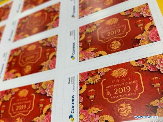 The Year of the Pig themed stamps are displayed in Sao Paulo, Brazil, Feb. 15, 2019. A series of stamps were published by local post office to celebrate the Year of the Pig. (Xinhua)
