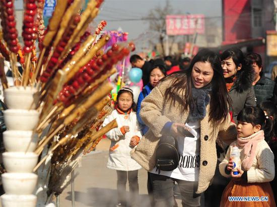 Tourists walk past booths selling tanghulu, a traditional Chinese snack of candied fruit, during an activity to greet the upcoming Lantern Festival in Lihua Village of Renqiu, north China's Hebei Province, Feb. 17, 2019. The traditional Chinese Lantern Festival falls on Feb. 19 this year. (Xinhua/Mu Yu)